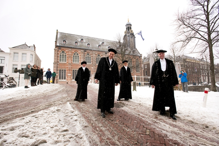 A group portrait of Carel Stolker, Hester Bijl, Annetje Ottow and the beadle, all in academic dress, in front of a snowy Academy Building.